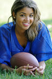 Biracial female football player 1. Pretty female biracial football player in blue mesh jersey laying in grass - looking at viewer stock photo
