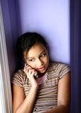 Biracial Girl on Cell Phone. Biracial beauty talking on cell phone in her bedroom window seat royalty free stock image