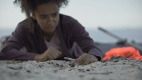 Biracial girl coughing lying on sand, refugee survived shipwreck, disaster. Stock footage stock footage