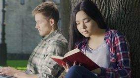 Biracial girl eagerly reading thrilling book without noticing guys loving looks. Stock footage stock footage