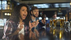 Biracial girl with friends watching sport game in bar, happy time together. Stock footage stock footage