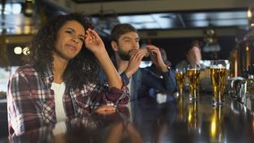 Biracial girl and male fans watching sport game in bar, disappointed with score. Stock footage stock footage