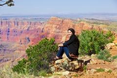 Biracial jugendlich Mädchen, das entlang Felsenleiste bei Grand Canyon sitzt Stockbild