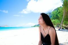 Biracial jugendlich Mädchen, das am hawaiischen Strand, Seitenprofil, smil sitzt Stockbild