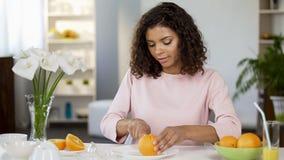 Biracial junge Frau, die orange, gesunden Lebensstil, frischen Saft, Vitamine schneidet stockbilder