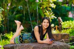 Biracial nastoletni dziewczyny lying on the beach na rockowym patrzeje telefonie komórkowym outdoors Obraz Stock