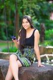 Biracial nastoletni dziewczyny obsiadanie na rockowym patrzeje telefonie komórkowym Obrazy Royalty Free