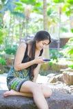 Biracial nastoletni dziewczyny obsiadanie na rockowym patrzeje telefonie komórkowym Fotografia Stock