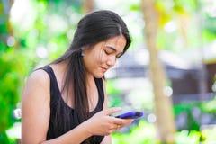 Biracial nastoletnia dziewczyna opowiada na telefonie komórkowym outdoors Zdjęcie Royalty Free