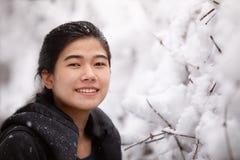 Biracial nastoletnia dziewczyna plenerowa w zimie cieszy się opad śniegu zdjęcie stock