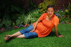 Biracial pregnant woman. A biracial highly pregnant woman with content smiling facial expression lying on the lawn in the garden and relaxing outdoors Stock Images