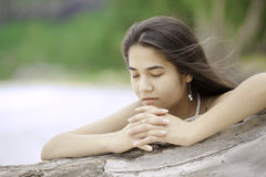 Biracial teen girl arms lying on beach relaxing by ocean water Stock Photos