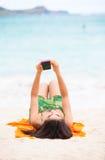 Biracial teen girl arms lying on beach relaxing by ocean water Stock Photography