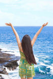 Biracial teen girl arms raised by ocean water in praise Stock Photo