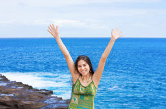 Biracial teen girl arms raised by ocean water in praise Royalty Free Stock Photo