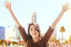 Biracial teen girl arms raised, urban background Stock Photography