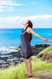 Biracial teen girl on cliff, arms outstretched by ocean Royalty Free Stock Photos