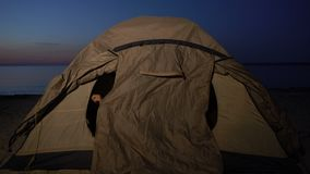Biracial teen girl hiding in tent when lit by flashlight, refugee camp on coast. Stock footage stock video footage
