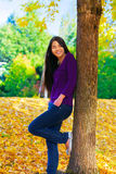 Biracial  teen girl leaning against tree, autumn leaves on groun Stock Image