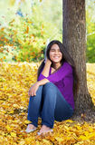 Biracial  teen girl leaning against tree, autumn leaves on groun Stock Images