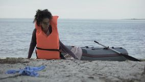 Biracial teen girl in lifejacket getting out of boat, refugee survived shipwreck. Stock footage stock video