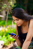 Biracial teen girl looking at cellphone in tropical setting Royalty Free Stock Images