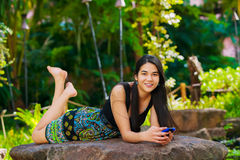 Biracial teen girl lying on rock looking at cellphone outdoors. Beautiful biracial Asian Caucasian teen girl lying on rock in tropical setting looking at Stock Image