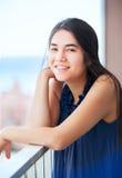 Biracial teen girl on outdoor highrise patio, urban ocean  backg Stock Photography