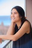 Biracial teen girl on outdoor highrise patio, urban ocean  backg Royalty Free Stock Photo