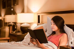 Biracial teen girl reading book  in bed at night Royalty Free Stock Image