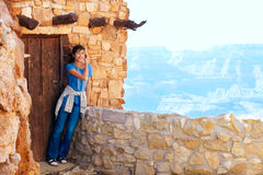 Biracial teen girl relaxing, leaning against rock wall overlooki Royalty Free Stock Images