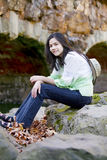 Biracial teen girl relaxing on rocks Royalty Free Stock Images