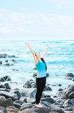 Biracial teen girl on rocks by ocean praising God. Slim, fit biracial Christian teen or young woman standing  on rocks by ocean in Hawaii lifting arms in praise Stock Images