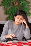 Biracial teen girl sitting at checkers board Royalty Free Stock Image