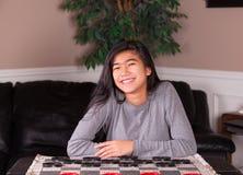 Biracial teen girl sitting at checkers board Royalty Free Stock Photo