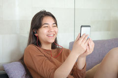 Biracial teen girl sitting on couch with smartphone, laughing Royalty Free Stock Image
