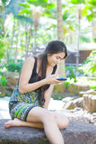 Biracial teen girl sitting on rock looking at cellphone. Beautiful biracial Asian Caucasian teen girl sitting on rock in tropical setting looking at cellphone Stock Photography