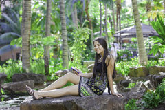 Biracial teen girl sitting on rock looking at cellphone. Beautiful biracial Asian Caucasian teen girl sitting on rock in tropical setting looking at cellphone Royalty Free Stock Image