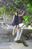 Biracial teen girl sitting on tree branch on beach Royalty Free Stock Image