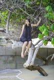 Biracial teen girl sitting on tree branch on beach Royalty Free Stock Image