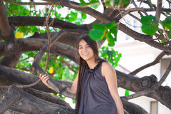 Biracial teen girl sitting on tree branch on beach Royalty Free Stock Images
