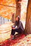 Biracial teen girl sitting under colorful maple trees in autumn. Biracial teen or young woman sitting under colorful maple leaves in autumn, with a carpet of royalty free stock photo