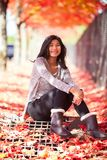 Biracial teen girl sitting under colorful maple trees in autumn Stock Images