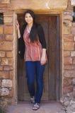 Biracial teen girl standing in brick doorway of home Stock Photography