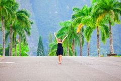 Biracial teen girl standing in middle of palm tree lined street Stock Images