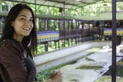Biracial teen girl standing over crocodile farm show in Thailand royalty free stock photo