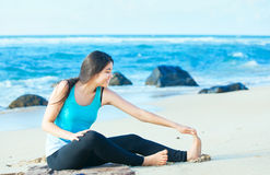 Biracial teen girl stretching and exercising on beach Royalty Free Stock Photos