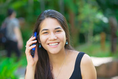 Biracial teen girl talking on cell phone outdoors. Beautiful biracial Asian Caucasian teen girl talking on cell phone outdoors with green foliage in background royalty free stock photos