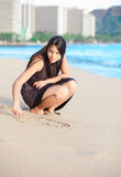 Biracial teen girl on Waikiki beach drawing in the sand Royalty Free Stock Photo