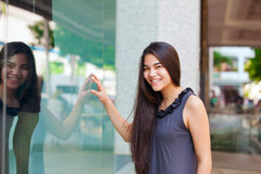 Biracial teen girl  window shopping in urban setting downtown Stock Image